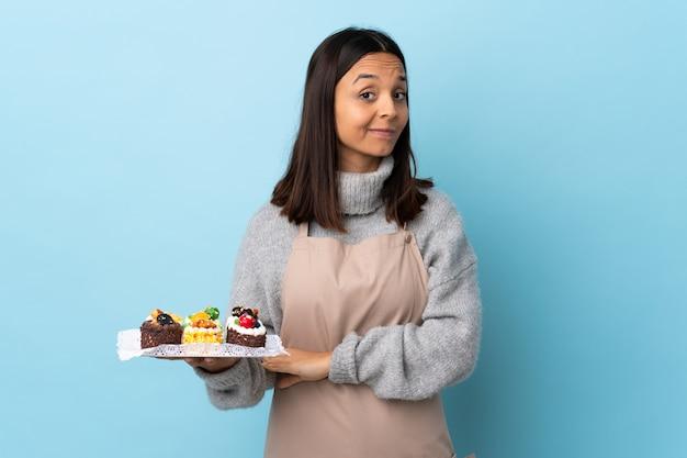 Konditor, der einen großen kuchen auf isoliertem blauem lachen hält