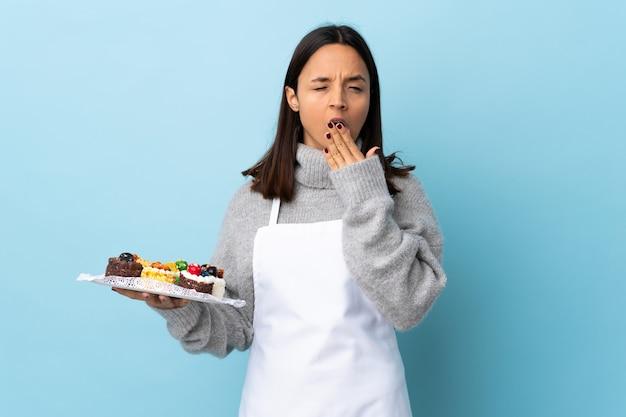 Konditor, der einen großen kuchen über isoliertem blauem gähnen hält und weit geöffneten mund mit hand bedeckt.