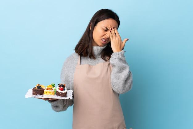 Konditor, der einen großen kuchen über isoliertem blauem raum mit kopfschmerzen hält