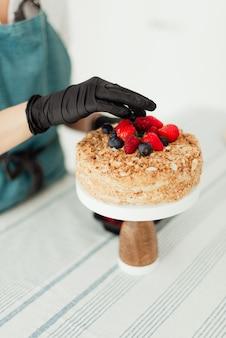 Konditor, der honigkuchen vorbereitet, der mit beeren-nahaufnahme-süßspeisen verziert wird