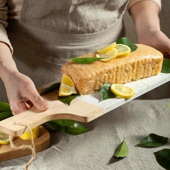 Konditor, der kuchen mit zitronenscheiben und blättern hält