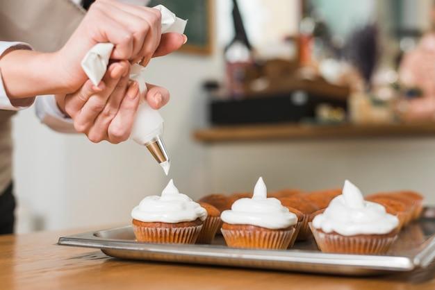 Konditor, der mit sahne köstliche muffins verziert