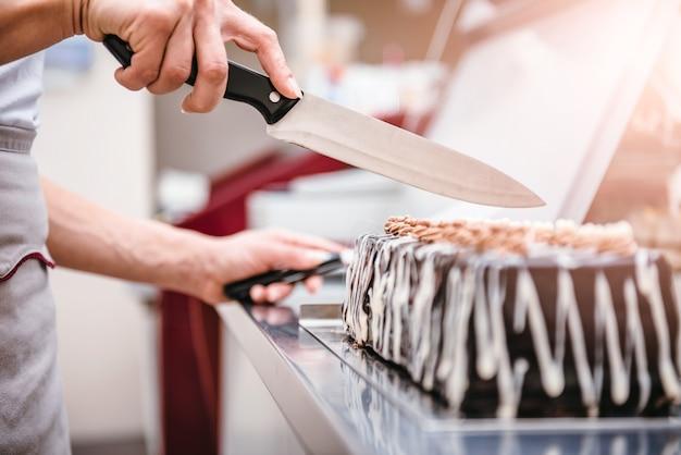 Konditor, der scheibe des kuchens nimmt