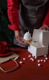 Konditor, der weiße papierbox mit weißem kuchen nahe rotem tisch hält