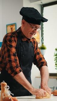 Konditor, der zu hause mit rohem teig in der modernen küche arbeitet, die das rezept aufzeichnet. pensionierter älterer bäcker mit bonete, der zutaten mit gesiebtem mehl knetet, um traditionelles brot zu backen.