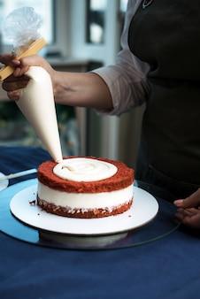 Konditor drückt beige sahne auf rotem samtkuchen zusammen. die frau verziert den kuchen mit süßer sahne