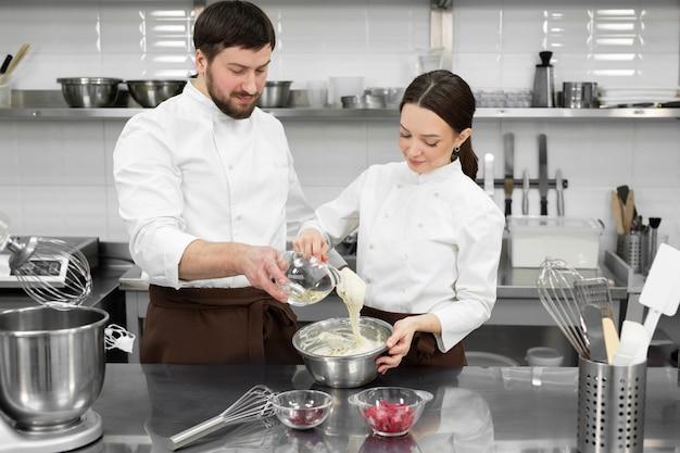 Konditor ein mann und eine frau in einer professionellen küche bereiten einen biskuitkuchen zu, mischen die zutaten