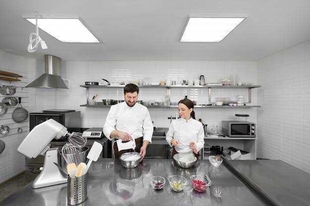 Konditor ein mann und eine frau in einer professionellen küche bereiten einen biskuitkuchen zu