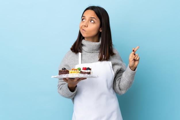 Konditor hält einen großen kuchen lokalisierten blauen hintergrund mit den fingern kreuzend