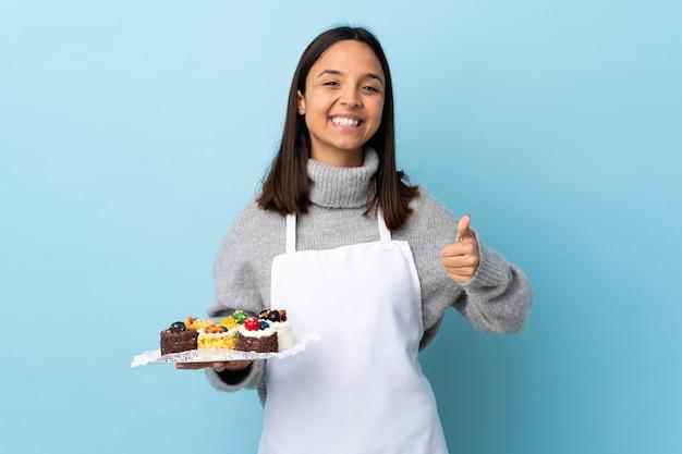 Konditor hält einen großen kuchen über der blauen wand, die imaginären leeren raum auf der handfläche und mit den daumen nach oben hält.