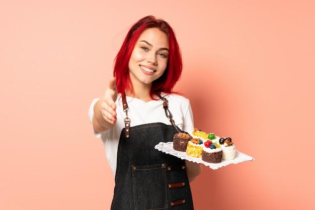 Konditor hält muffins an der rosa wand und schüttelt sich die hände, um ein gutes geschäft abzuschließen