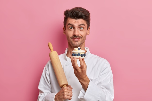 Konditor hält sahne leckeren kuchen, erzählt rezept von köstlichen süßwaren, arbeitet im café als koch, gekleidet in weiße uniform