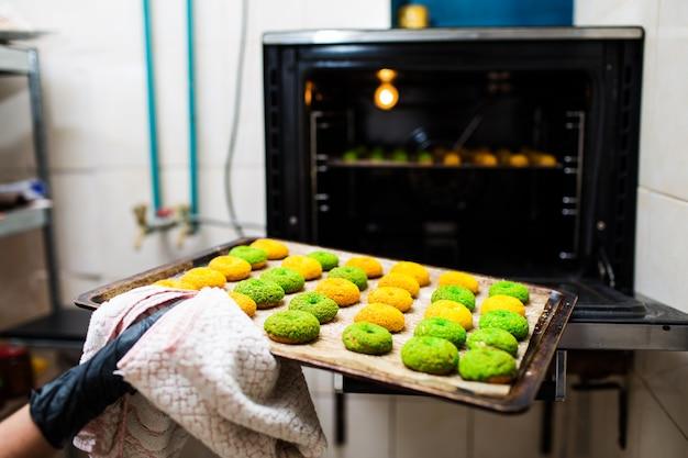 Konditor holt ein backblech mit runden grünen und gelben eclairs aus dem ofen. knusprige craquelure profiteroles