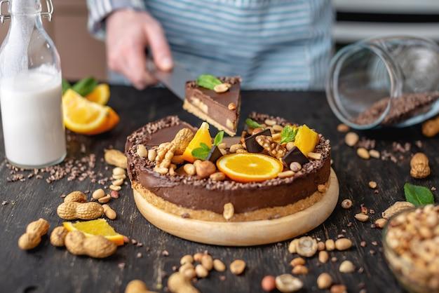 Konditor in der hand hält ein stück schokoladenkuchen mit orange