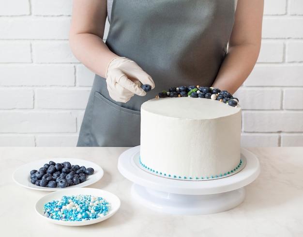 Konditor in schürze und handschuhen dekoriert einen weißen kuchen mit blaubeeren und süßigkeiten.
