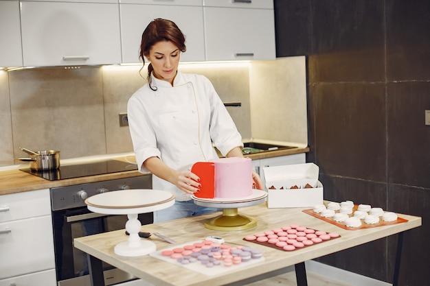 Konditor in uniform schmückt den kuchen