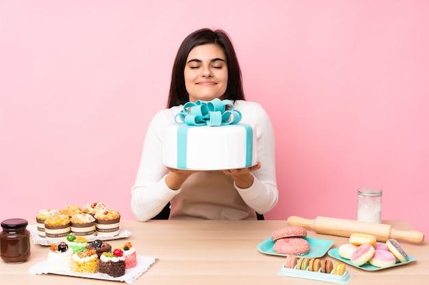 Konditor mit einem großen kuchen in einem tisch über rosa wand