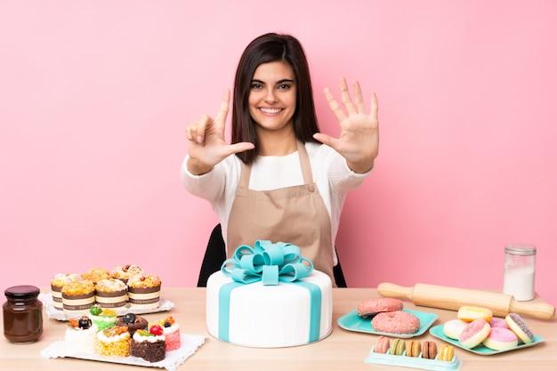 Konditor mit einem großen kuchen in einer tabelle über der lokalisierten rosa wand, die sieben mit den fingern zählt