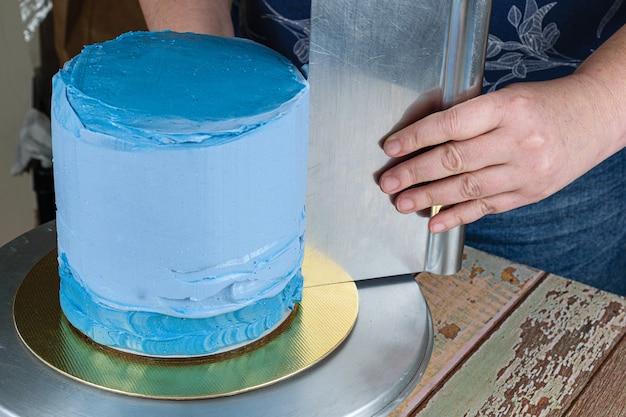 Konditor mit einem spatel an der seite des kuchens, um das zuckerguss zu verteilen.