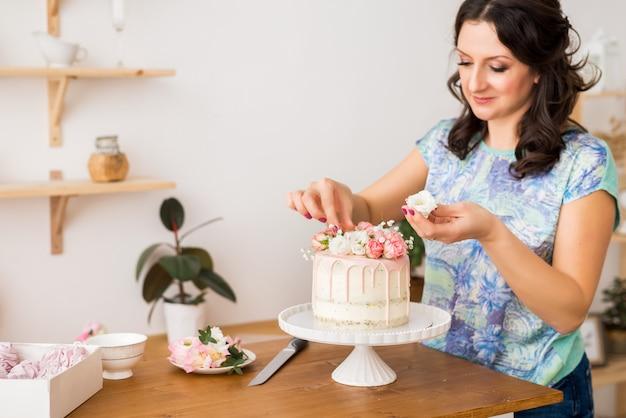 Konditor schmückt den kuchen mit blumen