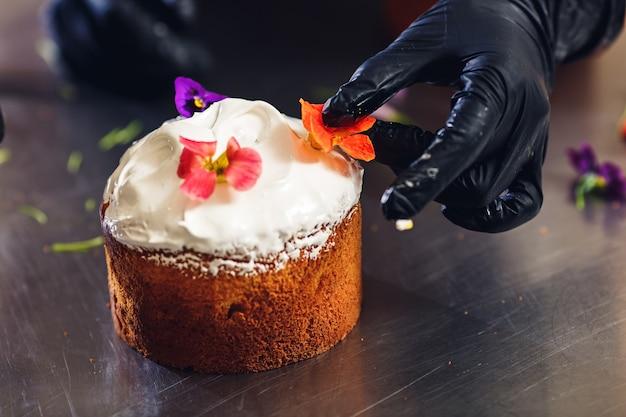Konditor schmückt osterkuchen mit zarten blumen.