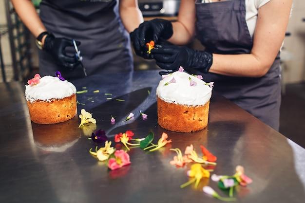 Konditor schmückt osterkuchen mit zarten blumen