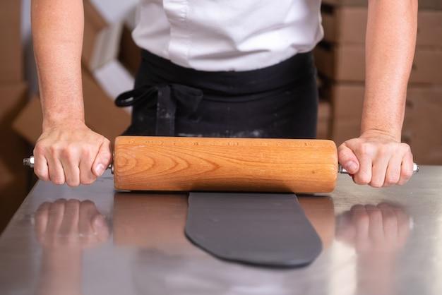 Konditor unter verwendung des nudelholzes, der fondant für die kuchenverzierung vorbereitet.