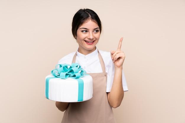 Konditorfrau, die einen großen kuchen über wand hält, der beabsichtigt, die lösung zu realisieren, während sie einen finger anhebt