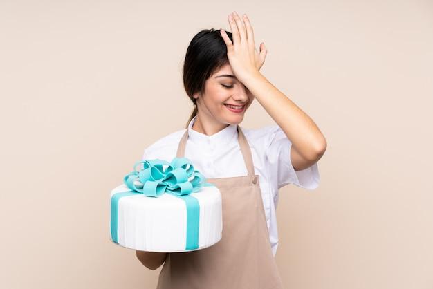 Konditorfrau, die einen großen kuchen über wand hält, hat etwas verwirklicht und die lösung beabsichtigt