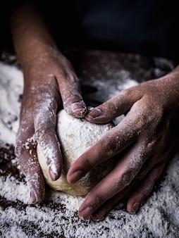 Konditorhand, die rohen teig mit dem besprühen des weißmehls über küchentisch knetet.
