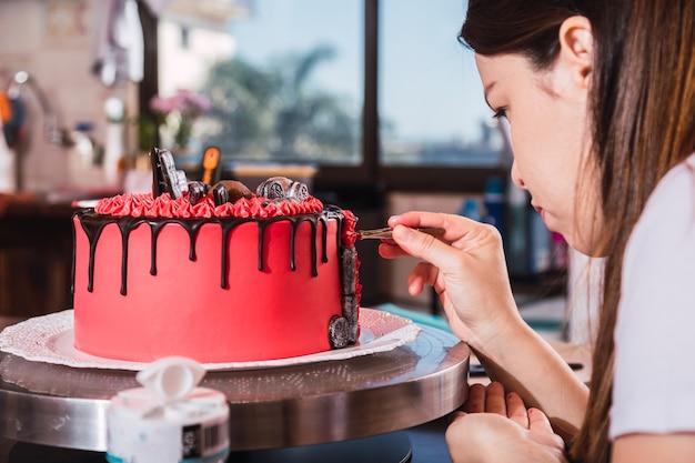 Konditorin der jungen frau, die einen appetitlichen kuchen mit schokolade verziert