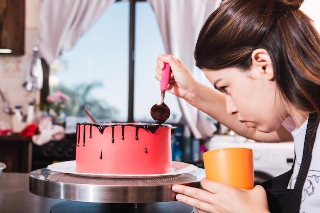 Konditorin der jungen frau, die einen kuchen mit schokolade verziert
