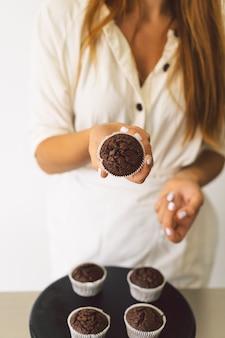 Konditormädchen bereitet zutaten für ein cupcake-konzept zum kochen von mehlprodukten oder desserts vor