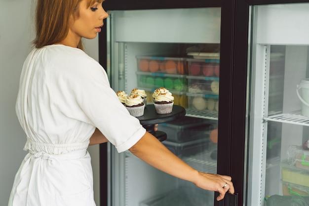Konditormädchen legt den cupcake in den gefrierschrank
