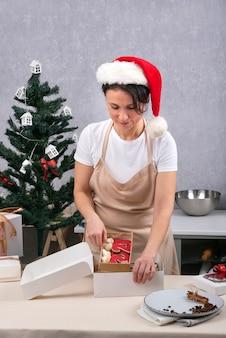 Konditorpackungen geschenkbox mit leckeren backwaren. porträt der frau im neujahrshut in der küche. vertikaler rahmen.