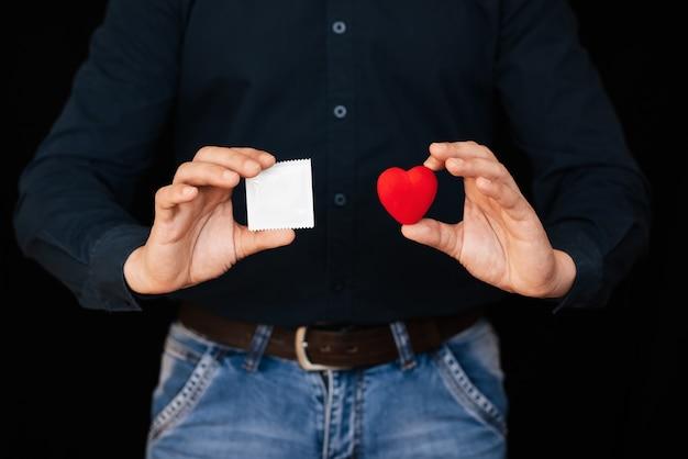 Kondom und ein rotes herz in den händen eines mannes