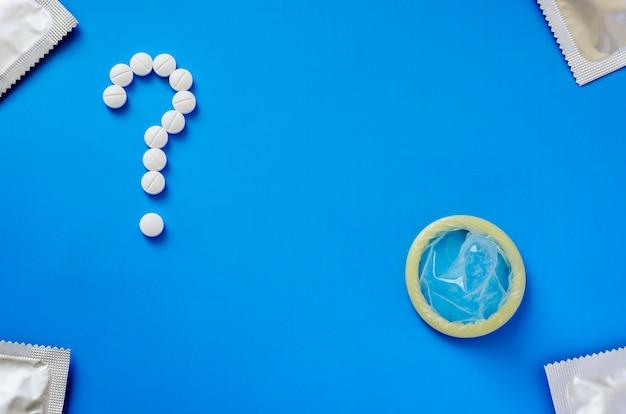 Kondom und fragezeichen von den tabletten auf einem blauen hintergrund