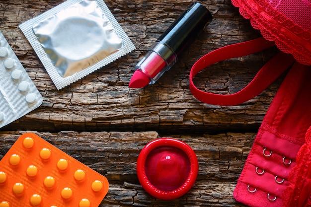 Kondome und antibabypillen auf einem hölzernen hintergrund