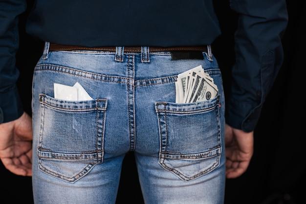 Kondome und banknotengeld in den jeans der gesäßtaschenmänner