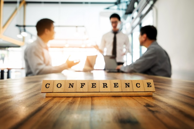 Konferenz wort auf holz tisch mit business-team arbeit diskussion zusammen konzept im hintergrund.