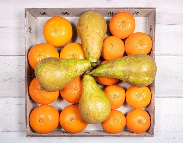 Konferenzbirnen mit mandarinen und clementinen in einem alten holztablett auf altem holzboden