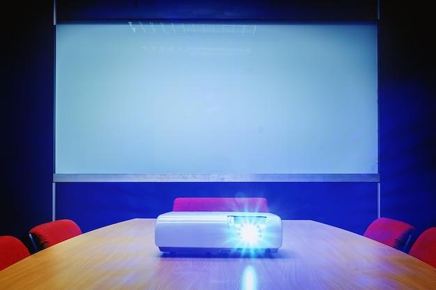 Konferenzzimmer mit blauem licht vom projektor auf dem tisch