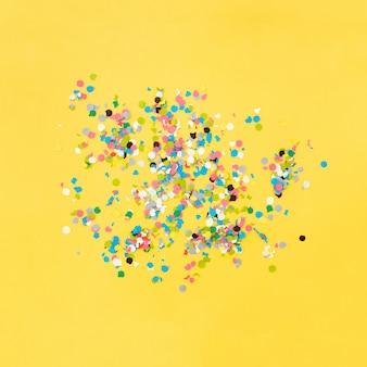 Konfetti auf gelbem grund nach der party