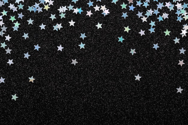 Konfetti der fallenden schillernden silbernen sterne auf schwarzem festlichem hintergrund