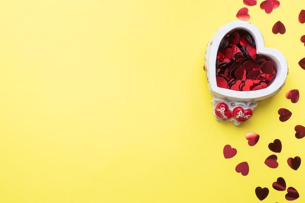 Konfetti der roten herzen in einem keramikständer in der form eines herzens auf einem gelben hintergrund. weihnachtskarte zum valentinstag. flach liegen.
