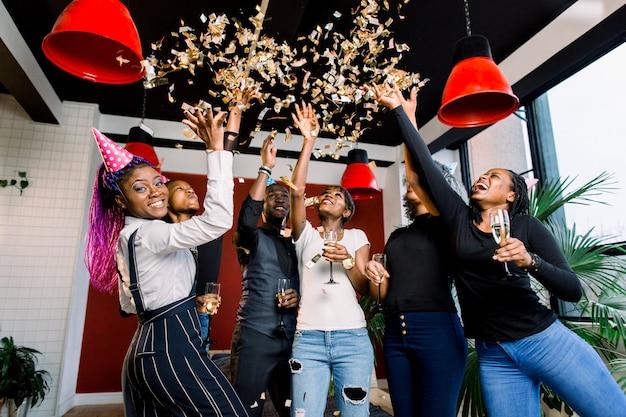 Konfetti fliegen um gruppe von afrikanern, die eine party mit l getränken in ihren händen feiern