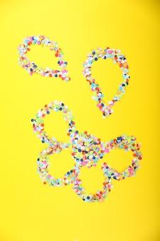 Konfetti in form einer blume auf gelbem hintergrund