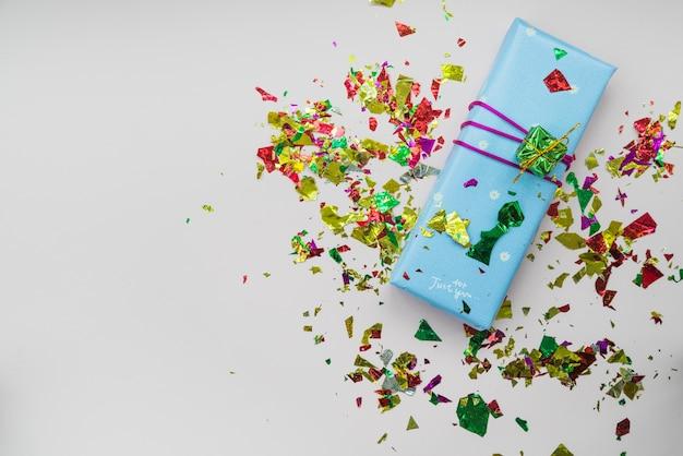 Konfetti über der eingewickelten geschenkbox gegen weißen hintergrund