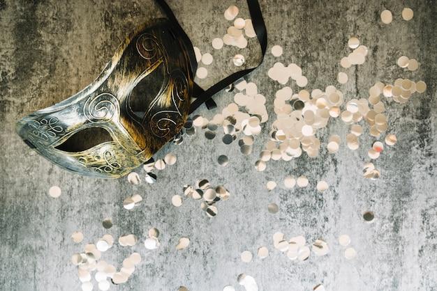 Konfetti und maske auf grauem hintergrund