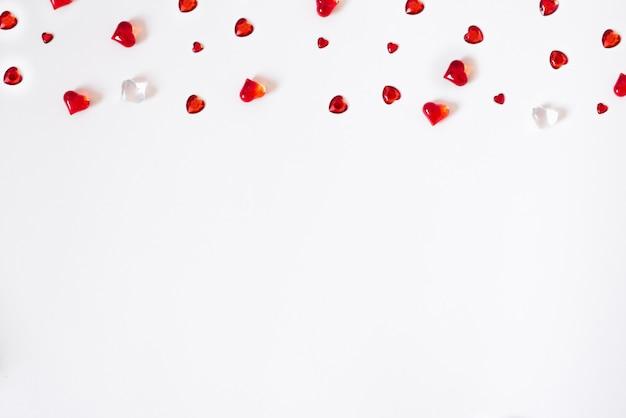 Konfetti von roten herzen. streuung einer in verlegenheit gebrachten grenze auf einem weißen valentinsgrußhintergrund